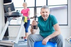 Senior sportsman sitting on fitness ball with sport bottle, sportswoman on treadmill behind Stock Photography
