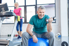 Senior sportsman sitting on fitness ball and training with dumbbell, sportswoman on treadmill behind Stock Photo