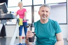 Senior sportsman sitting with sport bottle, sportswoman on treadmill behind Royalty Free Stock Image