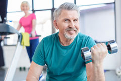 Senior sportsman sitting and training with dumbbell, sportswoman on treadmill behind Stock Images