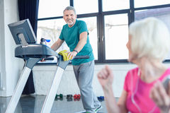 Senior sportsman training on treadmill, senior sportswoman on foreground Royalty Free Stock Photography