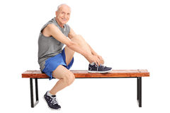 Senior in sportswear tying his shoelaces. Studio shot of a cheerful senior in sportswear tying his shoelaces seated on a bench and looking at the camera isolated Stock Photos