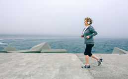 Senior sportswoman with headphones running. By sea pier Stock Images