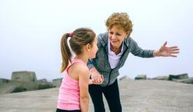 Senior sportswoman talking to little girl. By pier sea Stock Photography