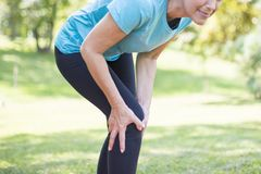 Senior sporty woman has knee pain. While workout royalty free stock images