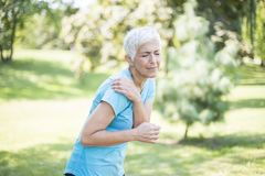 Senior sporty woman having shoulder pain. In the park stock photography
