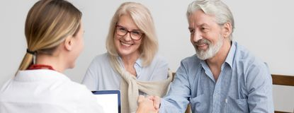 Senior spouses feels happy make deal shaking hands with agent royalty free stock photo