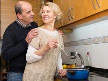 Senior spouses at modern kitchen Royalty Free Stock Photos
