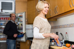 Senior spouses at modern kitchen Stock Images