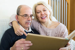 Senior spouses with picture album indoor Royalty Free Stock Photos