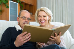 Senior spouses with picture album indoor Stock Image