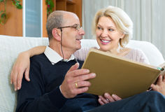 Senior spouses with picture album indoor Stock Photos