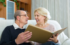 Senior spouses with picture album indoor Royalty Free Stock Image