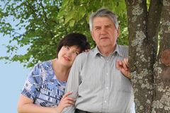 Senior standing, his daughter embracing him Stock Photo