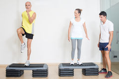 Senior step exercise. Physical therapist showing step exercise to couple of seniors Stock Image