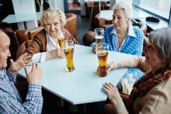 Senior storyteller entertaining his female friends Royalty Free Stock Images