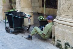 Street sweeper sitting down in a porch next to his cart mending a bag. Senior street sweeper sitting down in a porch next to his cart mending a bag, Havana, Cuba Stock Images
