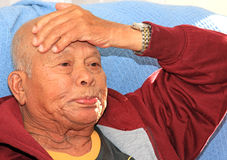 Senior Stress. Face shot of a senior Filipino man sat up on a recovery bed holding his head worried Stock Photo