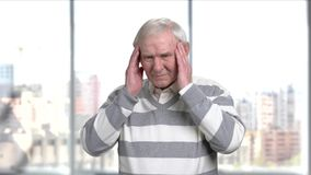 Senior stressed man suffering from headache. Elderly man rubbing his temples having a headache, blurred background stock video