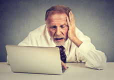 Senior stressed man working on laptop sitting at table isolated on gray wall background. Portrait senior stressed man working on laptop sitting at table isolated Royalty Free Stock Images