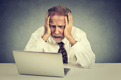 Senior stressed man working on laptop sitting at table Stock Image
