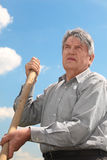 Senior in striped shirt with shovel Royalty Free Stock Photos