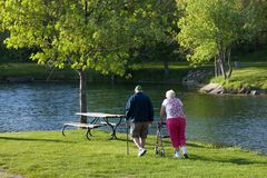 Senior Stroll by the Pond. SYCAMORE, ILLINOIS - May 23, 2014: An elderly couple walking to a picnic bench by a pond in the afternoon at Sycamore RV Park in royalty free stock image