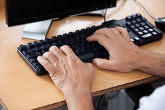 Senior Student Using Computer In Classroom. Cropped hands of senior male student using computer in classroom Stock Photos