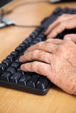 Senior Student Using Keyboard In Classroom. Cropped hands of senior male student using keyboard at desk in classroom Royalty Free Stock Photos