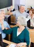 Senior Students Cheering In Computer Class. Happy senior students cheering in computer class Royalty Free Stock Image