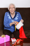 Senior stuffing christmas stocking Stock Photography