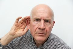 Senior suffering from deafness. Man asks to repeat the question royalty free stock photo