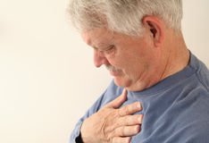 Senior suffers from heartburn or chest pain Stock Photos