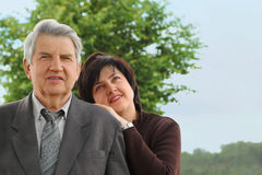Senior in suit, his daughter leans on his shoulder Stock Photo
