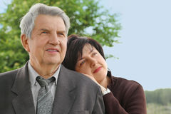 Senior in suit, his daughter leans on his shoulder Stock Photos