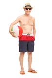 Senior with sunglasses holding a beach ball Stock Image