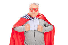 Senior in superhero costume tearing his shirt. Isolated on white background Stock Photo