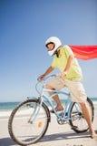 Senior superhero riding bike Stock Photos