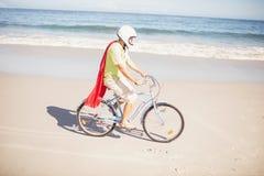 Senior superhero riding bike Stock Images