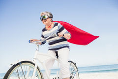 Senior superwoman on a bike Royalty Free Stock Photography
