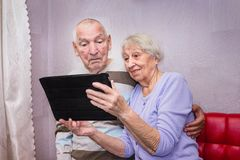 Senior couple with tablet relaxing at home. stock photo