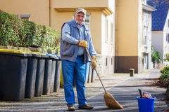Senior sweeping sidewalk with broom Stock Photo