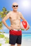 Senior in swim shorts holding beach ball at a beach Stock Photos