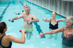 Senior swimmers and instructor lifting dumbbells in swimming pool. High angle view of senior swimmers and instructor lifting dumbbells in swimming pool Stock Images