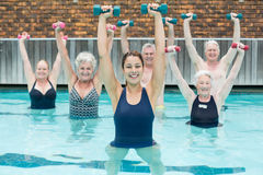 Senior swimmers lifting dumbbells in swimming pool. Portrait of trainer with senior swimmers lifting dumbbells in swimming pool Stock Photo