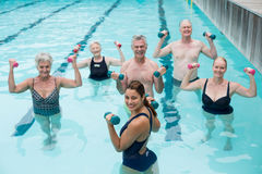 Senior swimmers and trainer lifting dumbbells in swimming pool Royalty Free Stock Photo
