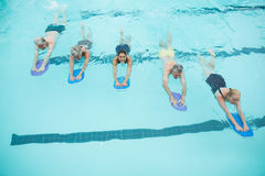 Senior swimmers and trainer swimming with kickboards in pool Stock Photography