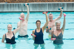 Senior swimmers with trainer during weightlifting training. Portrait of senior swimmers with trainer during weightlifting training in swimming pool Stock Photos