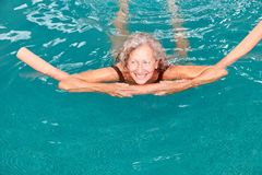 Senior in the swimming pool is doing aqua fitness. Smiling senior woman in the swimming pool is doing aqua fitness with buoyancy aid stock image