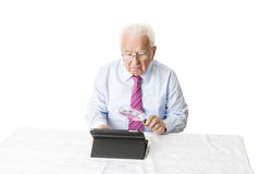 Senior with tablet and magnifying glass. Senior using a tablet computer with a magnifying glass Stock Images
